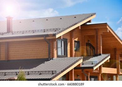 Part of the facade of a wooden house in modern style and sun beams