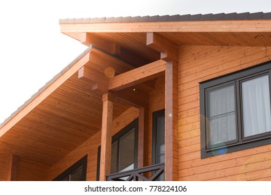 Part of the facade of a wooden house in modern style and sun rays