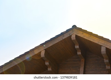 Part of the facade of a wooden house. Ridge beam and roof lining and sun rays.