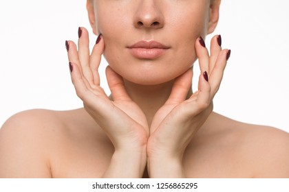 Part of the face of a relaxed and serene naked beautiful girl holding fingers on her cheeks during cosmetic procedures isolated on white background. Lifestyle. Beauty concept .