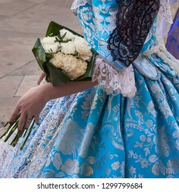 part of a faller woman costume, blue with flowers and black mantilla, during the offering to the virgin of the homeless, at the parties of the faults of Valencia in Spain