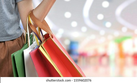 Part of female hand holding shopping paper bags with blurred background of shopping mall area in department store, city lifestyle and business concept