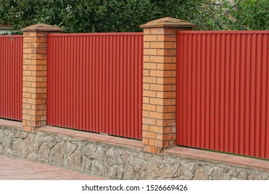 part of the fence on the street of brown bricks and red metal