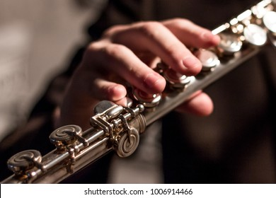 Part of a flute with the right hand of a man on a flute close-up. Shallow depth of field. Musical theme. Wind instrument. Modeling light.