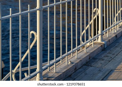 part or fragment of an iron handrail of the bridge with a wooden scaffold closeup