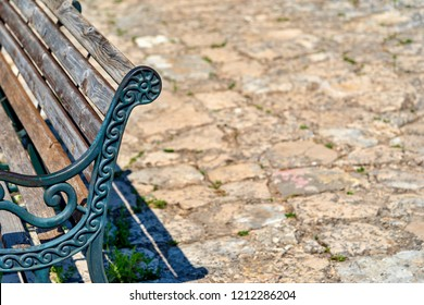 part or fragment of an old ancient bench closeup on an indistinct background of a stone pavement