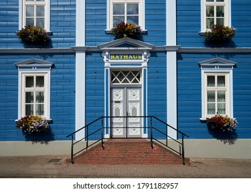 """part of the freshly painted blue facade and front door of the historic town hall in Soltau (Germany) - the word """"Rathaus"""" means translated """"town hall"""""""