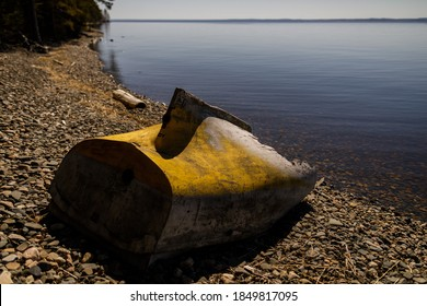 part of the fuselage of a broken boat or cutter lies overturned on the shore of a reservoir, destroyed water transport