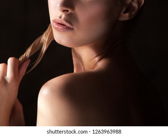 Part of girl beauty face and body with natural lips, clean skin. Black background
