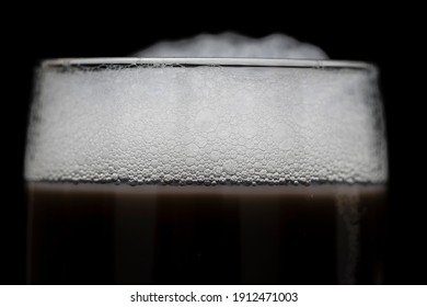 Part of a glass of cold drink with white froth, close up
