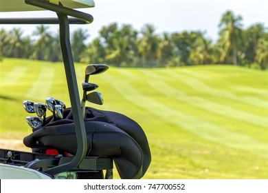 A part of golf car and golf equipment with green grass fairway background
