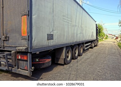Part of a gray truck with a container on the road