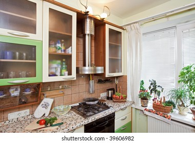 Part of Green Kitchen interior with many utensils and window