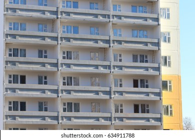 Part of grey apartment building of bearing-wall construction with balconies at sunny day