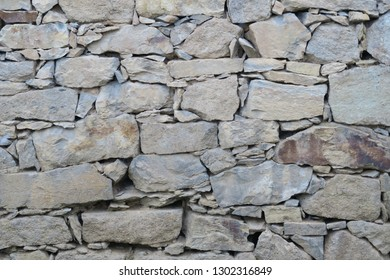 a part of a grey sand stone stone wall