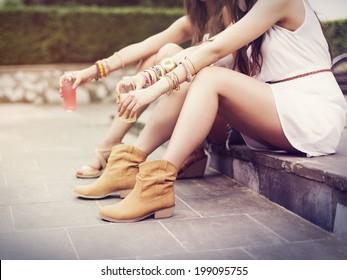 Part of hippie women sitting on curb