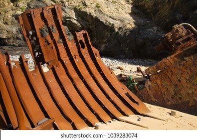 Part of the hull of a wrecked push boat looking like metal rusted ribs buried into the sand next to the boat bow.
