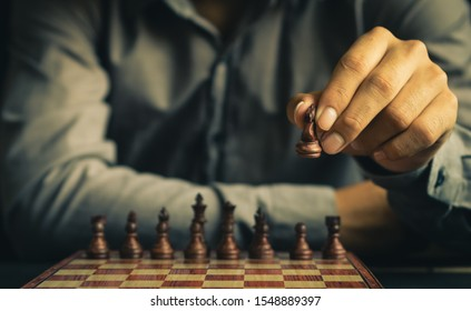 part of human hand moves chess figure on chess board in retro color tone