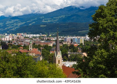 Part of the Innsbruck skyline during the day. Showing buildings, churches, mountains and clouds