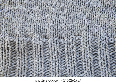 Part of a knit project, sweaters close-up, top view. Classic loops made of gray threads of Italian wool yarn. The concept of knitting, needlework, handmade. Texture background.