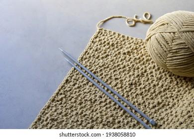 part of knitted work in beige soft yarn, grey background