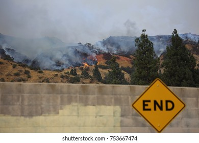 """Part of the """"La Tuna Fire"""" Burning Beyond an """"End"""" Road Sign just outside Los Angeles."""