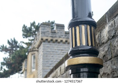 Part of a Lamp Post, black and gold color, blurred wall and tower in background, shallow depth of field, Wales Cardiff Winter 2019