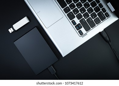 Part of the laptop with an external hard drive and a flash drive on a black background, top view. The concept of mobile data storage