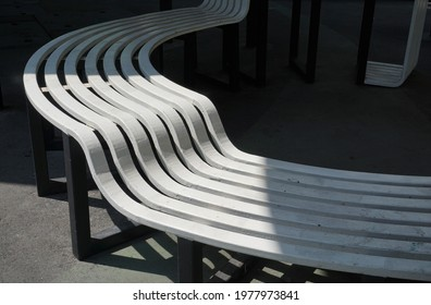 Part of the large white slatted chair has a different curve shape and different level. It was sunny at the lower curves.