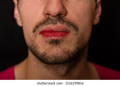 part of the lips is painted with red lipstick on the face of a gay guy. Inaccurate stubble and thick mustache.  black background
