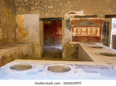Part of living room (bakery Thermopoly) with frescoes on walls and clay vats built into oven, which served as acks for food trade, in ruined city of Herculaneum, Pompeii, Naples, Italy.