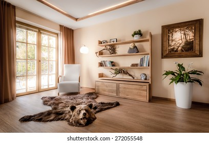 Part of the living room with the balcony doors bathed in the rays of the summer sun. The interior is decorated mostly with wooden features and hunting trophies. The room has a very warm feel.