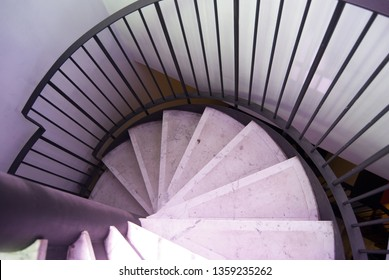 Part  of marm staircase spiralling down. Rounded stone staircase