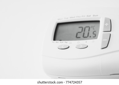 Part of a mdern white thermostat in a home