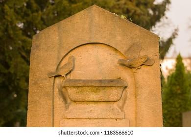 Part of a memorial stone displaying a birdbath and birds.