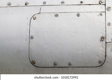 part of the metal structure made of a sheet of gray aluminum with rivets, the surface formed by corrosion and rust, Airplane airframe close-up