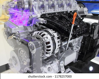 Part of model of new car DOHC engine - Camshaft timing meshanism, alternator, oil dipstick and intake collector of modern gasoline motor in cut section