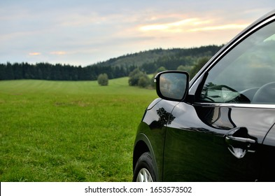 Part of modern black SUV crossover car vehicle in nature