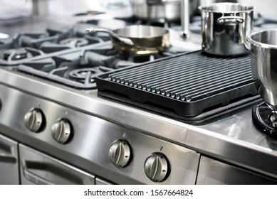 Teil einer modernen Küche im Restaurant oder Hotel mit professioneller Ausstattung - Gasherd aus Stahl, Töpfe und Pfannen ( Low DOF)