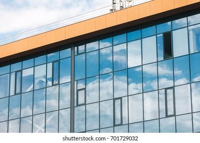 A part of modern office building with windows and cloudy sky background.