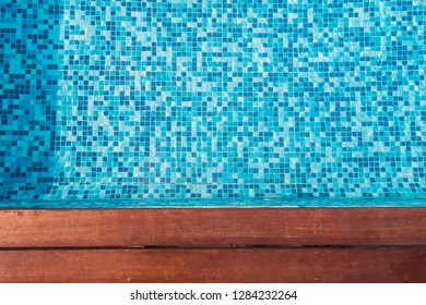 A part of modern swimming pool with wooden border top view.