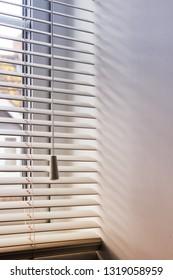 Part of a modern window blind with dappled sunlight