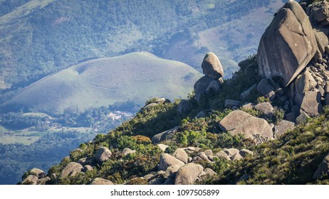 Part of a mountain with green nature and raw rocks illuminated by the sun light with more mature in the distant background.