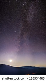Part of a night sky with stars and Milky Way on with Moon and mountains below