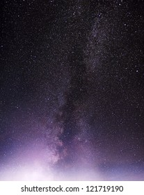 Part of a night sky with stars and Milky Way over violet clouds