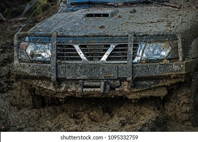 Part of offroad car stuck in deep mud on dark background. Bonnet, lights and bumper covered with dirt, close up. Wheels slipping in deep rut. Extreme entertainment concept.