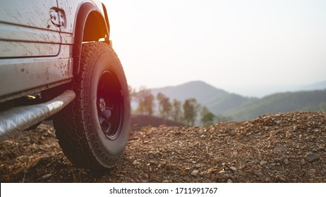 Part of an off-road vehicle on a pile of stones With sunset And has a beautiful mountain background.