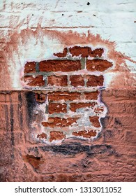 Part of an old brick wall with shabby plaster and paint