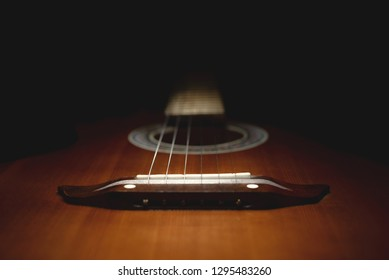 part of an old brown guitar with strings on a dark wooden background. Selective focus