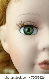 Part of an old doll's face showing half of nose, lips and green eye.